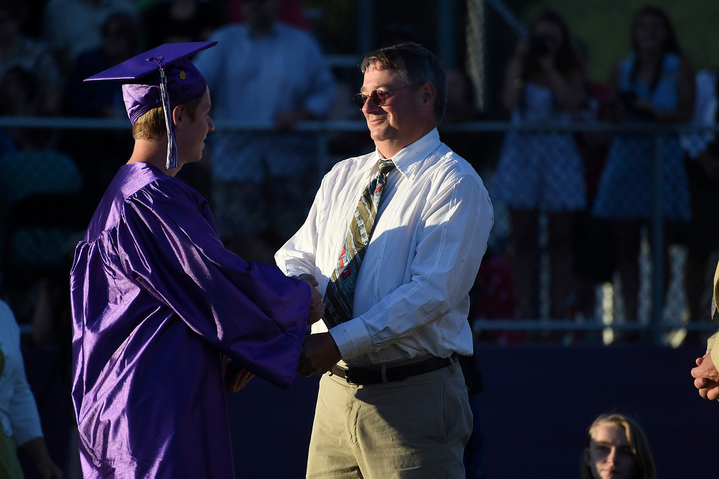 Description of . Kayla Rice/Reformer BUHS science teacher Chris Angell gives a diploma to his son at the BUHS graduation ceremony on Friday evening.