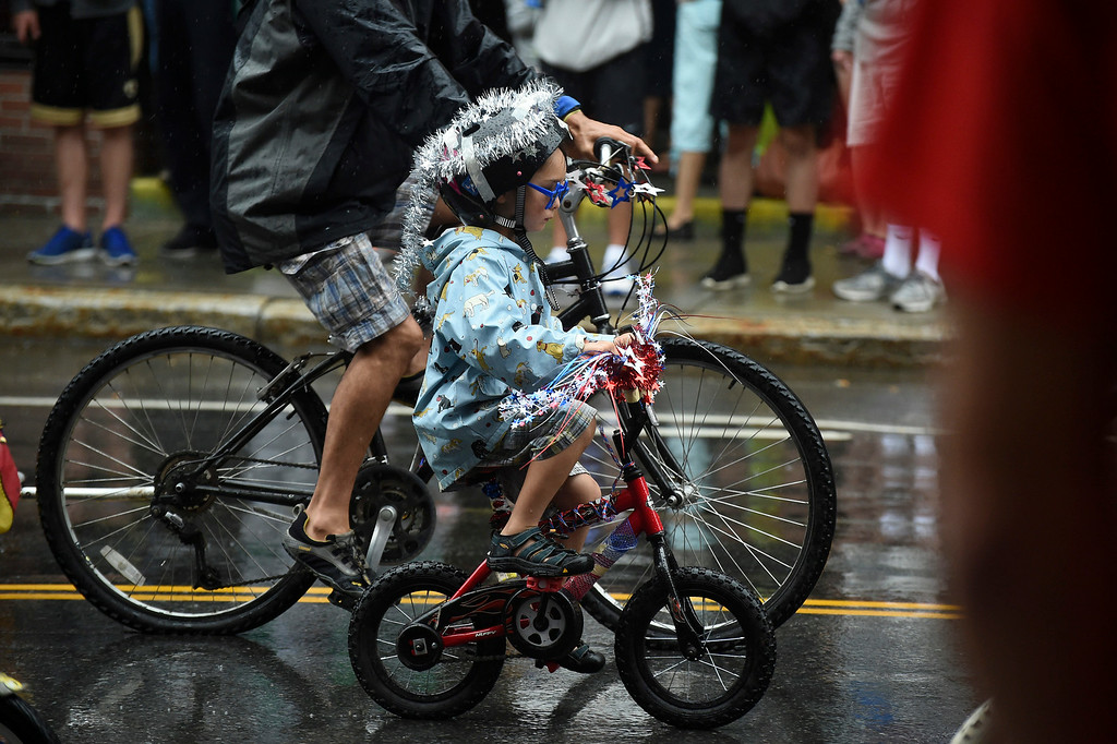 Description of . Kayla Rice/Reformer A child with a bedazzled bike rides down Main St. in the Fourth of July parade on Friday.