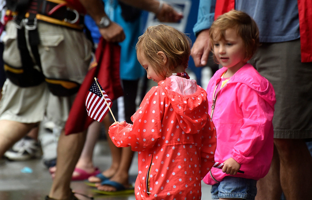 Description of . Kayla Rice/Reformer Alex and Emma Day, 3, of Brattleboro check out their new American flags while watching the Brattleboro Fourth of July parade on Friday.
