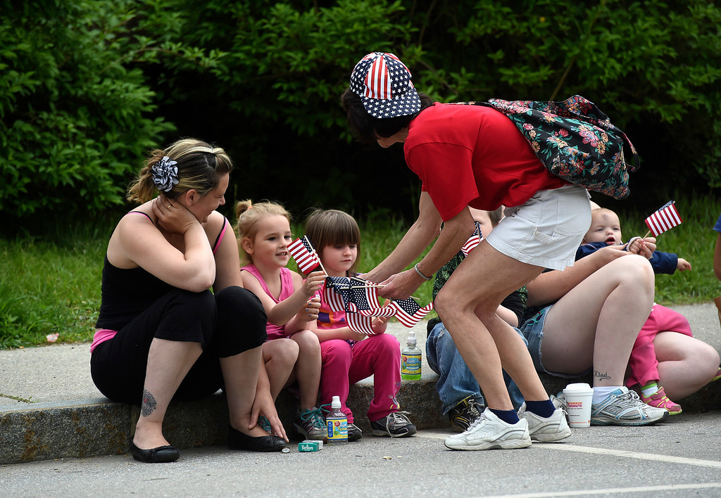 Description of . Kayla Rice/Reformer Karen Johnson hands out flags to cousins Hayla and Maddison Paligo, both 4, before the Hinsdale Memorial Day parade on Monday morning.