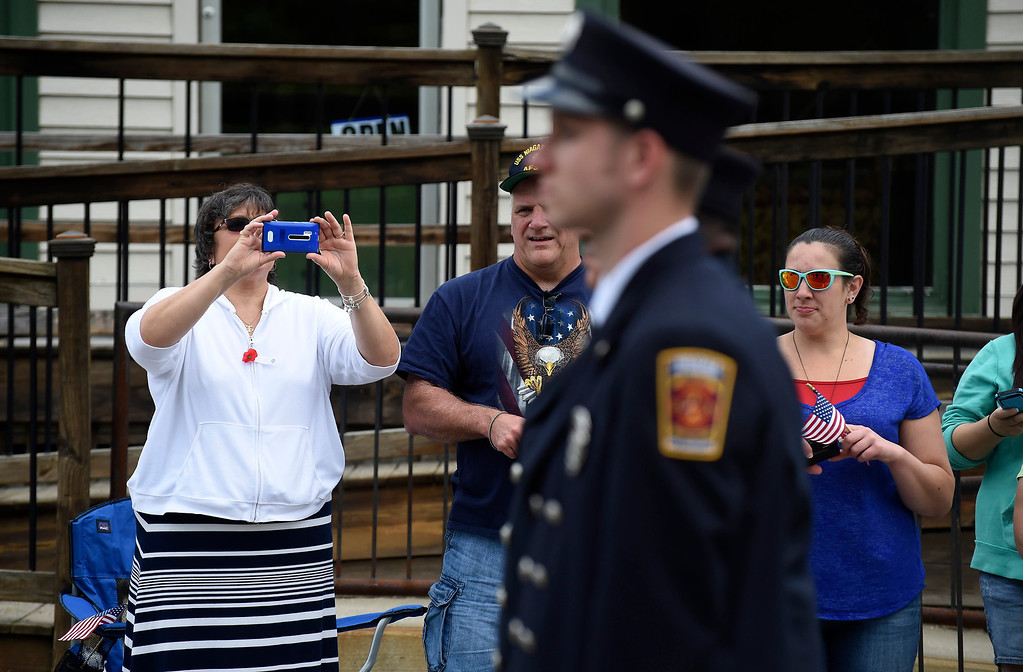 Description of . Kayla Rice/Reformer A woman takes a picture with her phone of the firefighters from the Hinsdale Fire Dept. walking in the Hinsdale Memorial Day parade on Monday morning.