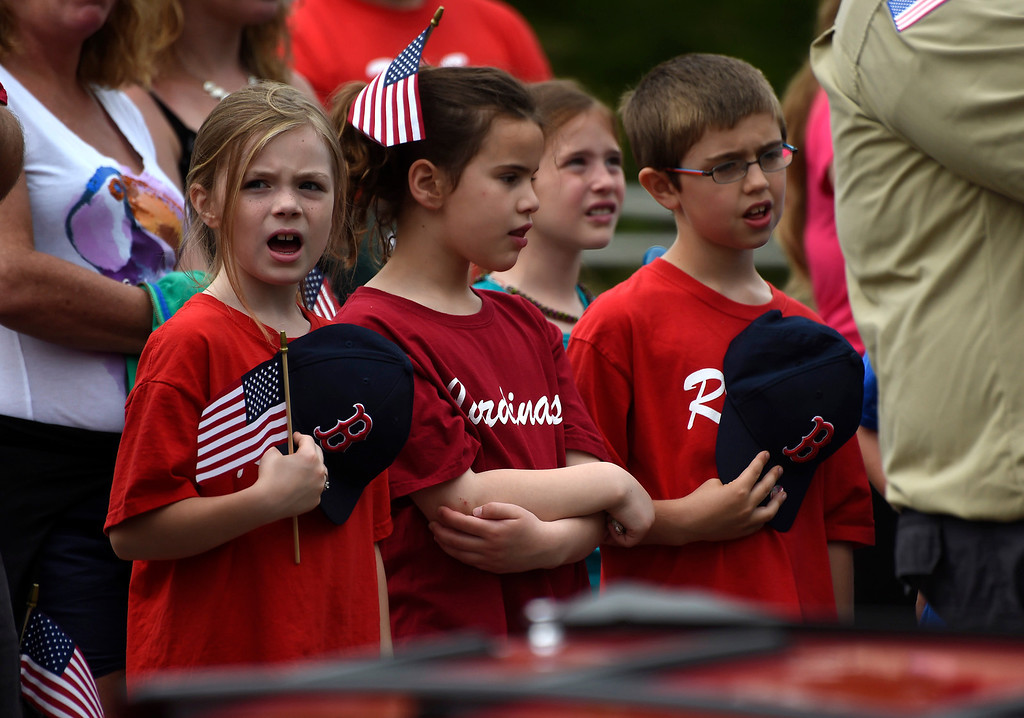 Description of . Kayla Rice/Reformer (L-R) Ashlyn Honeycutt, Adeline Nardolillo and Brayden Eastman, all 8 years old, sing along during the National Anthem after walking with their Coach Pitch baseball teams in the Hinsdale Memorial Day parade on Monday morning.