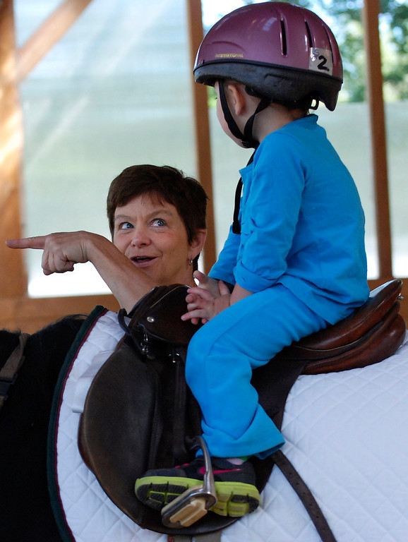 Description of . Kayla Rice/Reformer                                 Program Director Lorna Young works with Lexi Leland, 3, during Lexi's weekly horse therapy at Winchester Stables in Newfane.