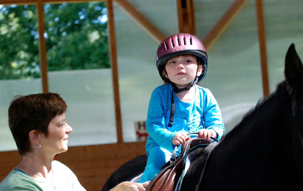 Description of . Kayla Rice/Reformer                                 Program Director Lorna Young (left) works with Lexi Leland, 3, during Lexi's weekly horse therapy at Winchester Stables in Newfane.
