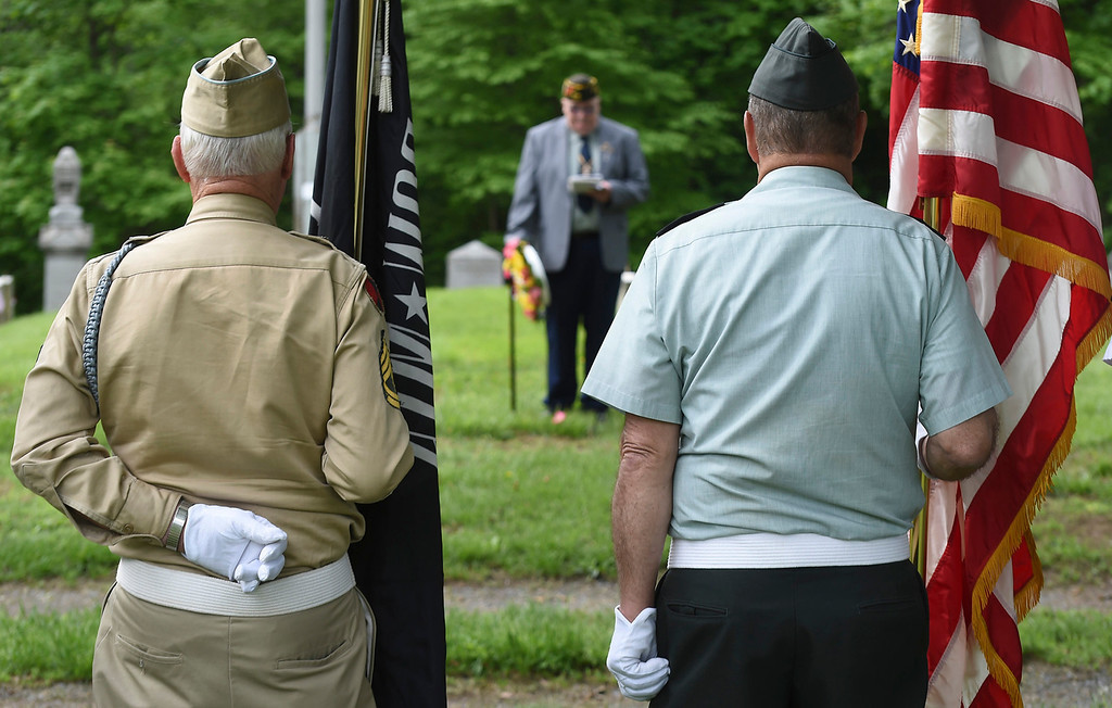 Description of . Kayla Rice/Reformer Local veterans stand with flags while American Legion chaplain E. David Wright speaks during a Memorial Day service in the Prospect Hill cemetery in Brattleboro on Monday morning.