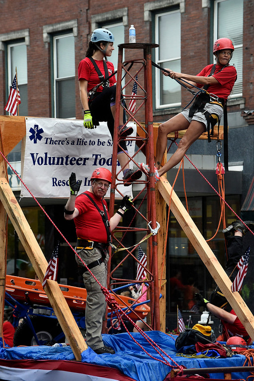 Description of . Kayla Rice/Reformer Rescue Inc. volunteers travel down the Brattleboro Fourth of July parade route on Friday.