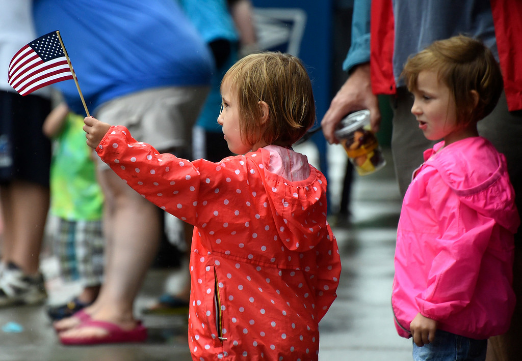 Description of . Kayla Rice/Reformer Alex Day, 3, of Brattleboro waves her American flag while watching the Brattleboro Fourth of July parade next to her twin sister Emma Day on Friday.