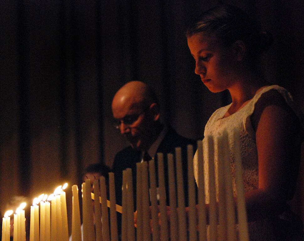 Description of . Kayla Rice/Reformer Kurn Hattin School student Chrystal Longe lights candles to symbolize the lives of local men and women lost at war during the school's Eighteenth Annual Veterans Day Observance.