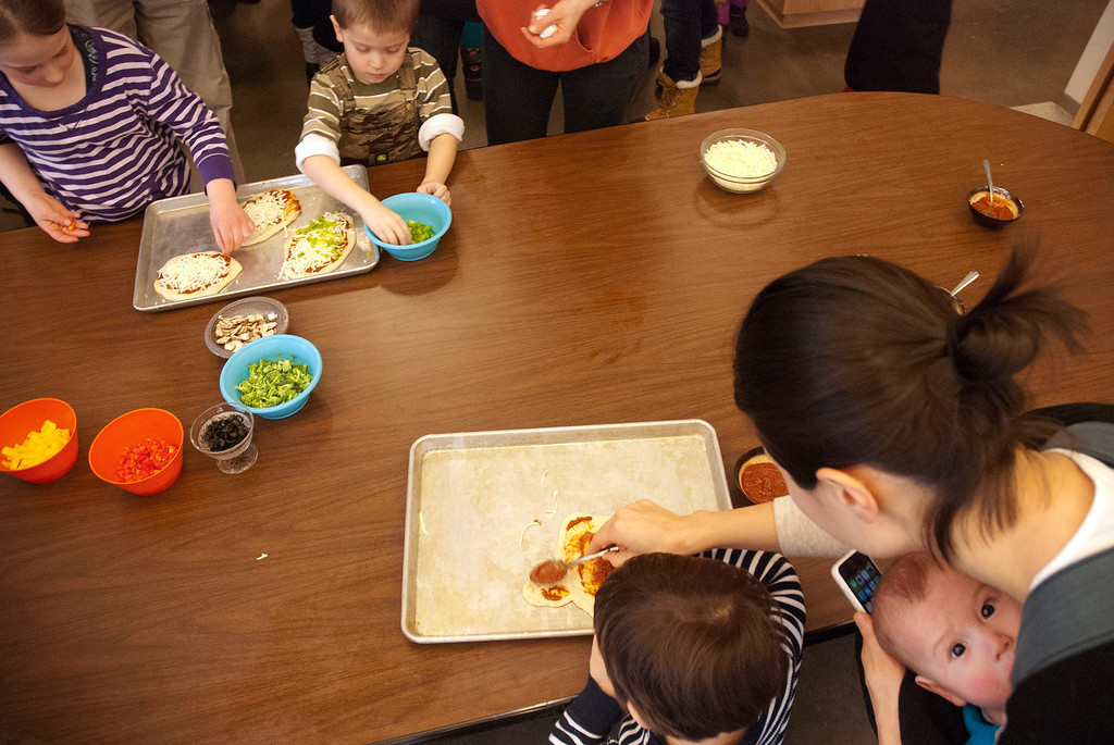 Description of . Kayla Rice/Reformer MJ Iams, 3, of Brattleboro gets some help from his mother, Nara Iams and baby brother Patrick Iams while spreading tomato sauce on his pizza crust during a cooking class held at the Brattleboro Food Co-Op for the Winter Carnival on Friday afternoon.