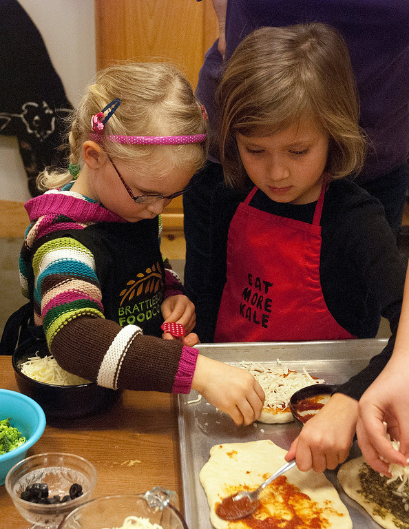 Description of . Kayla Rice/Reformer (L-R) Maeve Bald and Vivien McLouglin, both 5 and of Brattleboro, cover their pizza crusts with toppings during a cooking class held at the Brattleboro Food Co-Op for the Winter Carnival on Friday afternoon.