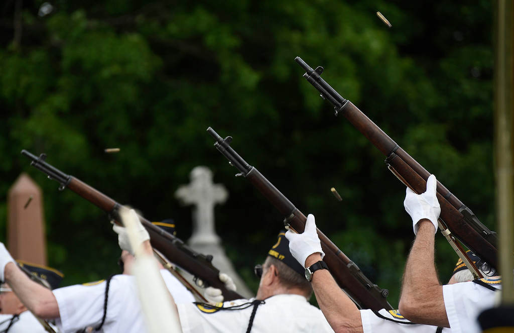 Description of . Kayla Rice/Reformer Members of the Brattleboro VFW Honor Guard shoot their rifles into the air during the Memorial Day service at St. Michael's cemetery in Brattleboro on Monday morning.