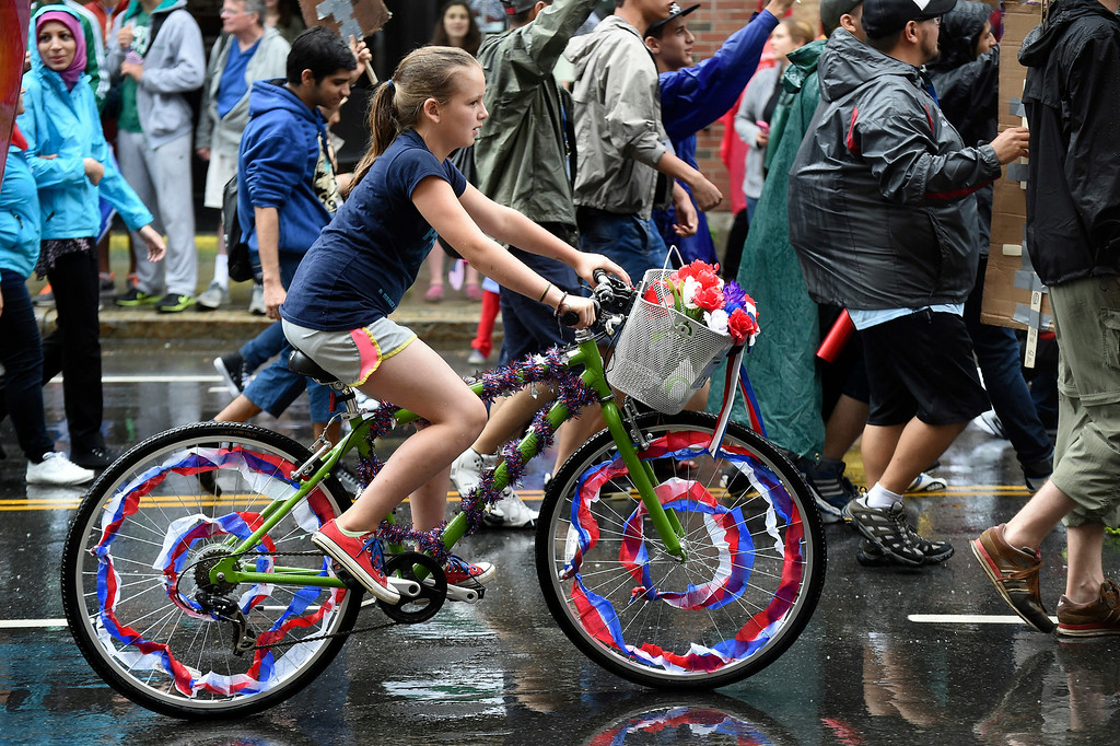 Description of . Kayla Rice/Reformer A girl rides her bike with the Governor's Institute of Vermont in the Brattleboro Fourth of July parade on Friday.