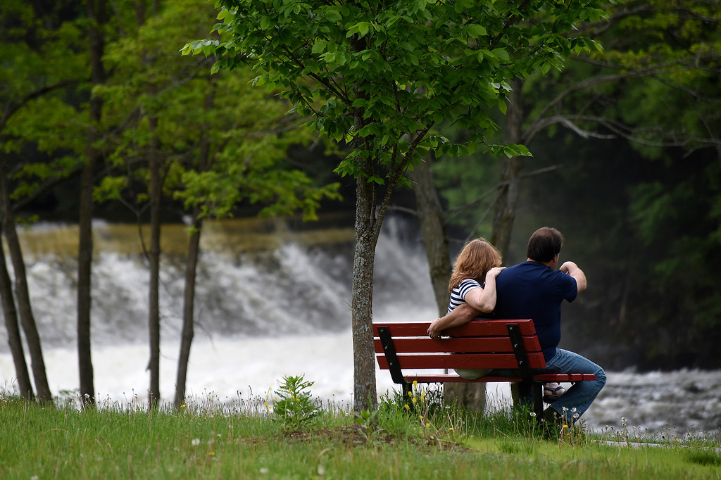 Description of . Kayla Rice/Reformer A couple sits on a bench overlooking the Ashuelot River Dam on Memorial Day before the town's parade.