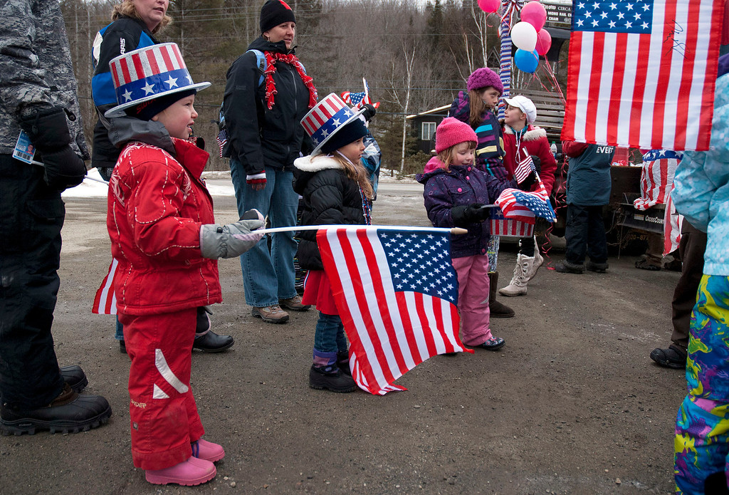 Description of . Kayla Rice/Reformer                                 Patriotically dressed children hold American flags for the