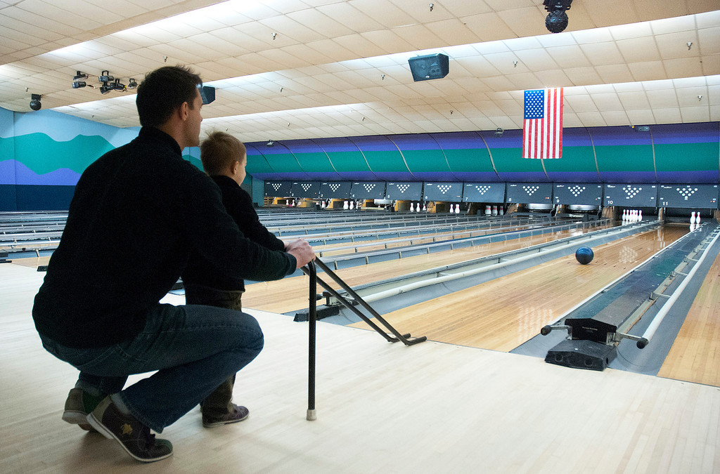 Description of . Kayla Rice/Reformer Keith Tylecki of Fairfax, Va. helps his son Andrew Tylecki, 3, bowl at Brattleboro Bowl on Tuesday afternoon.