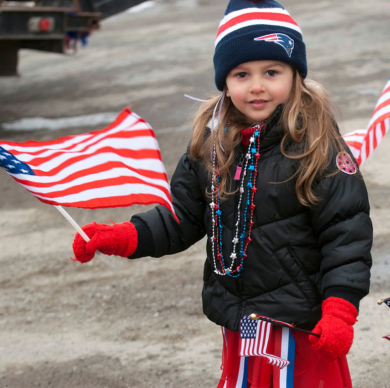 Description of . Kayla Rice/Reformer                                 A patriotically dressed girl holds American flags for the