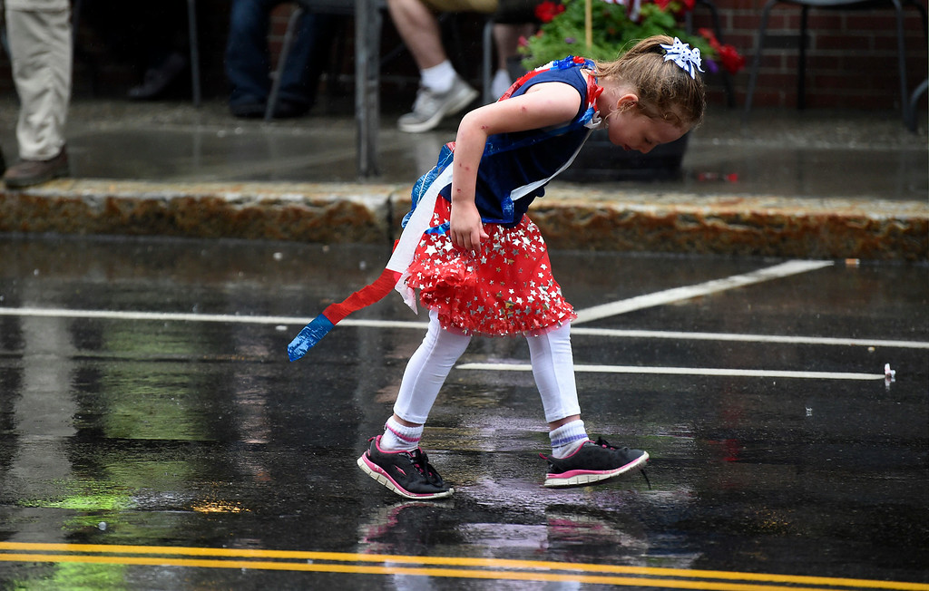 Description of . Kayla Rice/Reformer A girl checks out her shoes while walking in the Brattleboro Fourth of July parade on Friday.