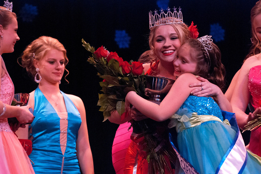 Description of . Kayla Rice/Reformer Kara Walsh gets a hug from 2013 Winter Carnival Princess Kyla Brown after being announced as the 2014 Winter Carnival Queen during the Queen's pageant on Friday evening.