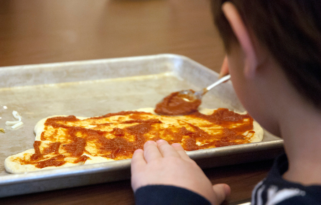 Description of . Kayla Rice/Reformer MJ Iams, 3, of Brattleboro puts tomato sauce on his pizza crust during a cooking class held at the Brattleboro Food Co-Op for the Winter Carnival on Friday afternoon.