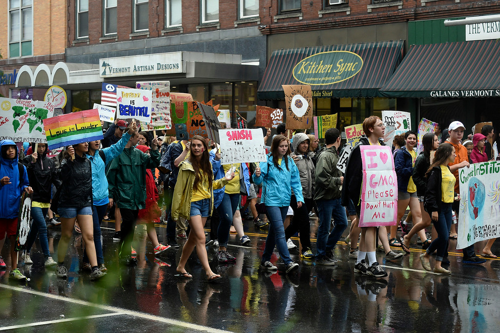 Description of . Kayla Rice/Reformer Students from the Governor's Institute of Vermont walk with signs in the Brattleboro Fourth of July parade on Friday.