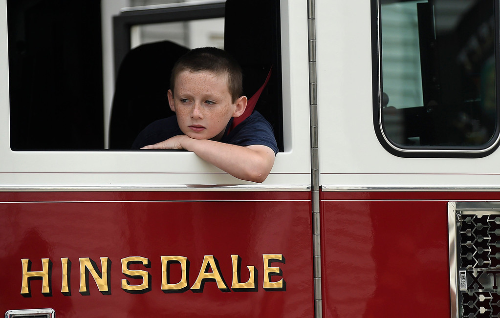 Description of . Kayla Rice/Reformer Zachery Gassett rides in a Hinsdale Fire Truck in the Hinsdale Memorial Day parade on Monday morning.