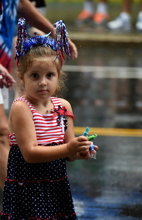 Description of . Kayla Rice/Reformer A girl prepares to throw a large handful of candy while walking in the Brattleboro Fourth of July parade on Friday.