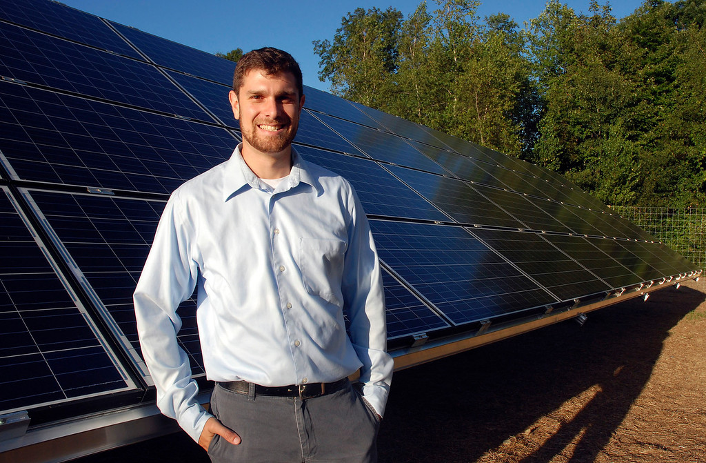 . Kayla Rice/Reformer                                 Nick Ziter, founder of SunFarm Community Solar, stands in front of a solar panel at the newly built community solar array in Putney.