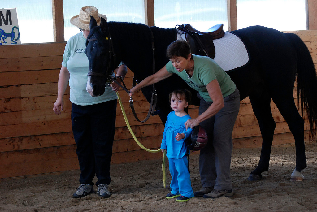 ". Kayla Rice/Reformer                                 Program Director Lorna Young (right) and volunteer Patsy Mehlhop (left) work with the horse ""Spot\"" and Lexi Leland, 3, during Lexi\'s weekly horse therapy at Winchester Stables in Newfane."