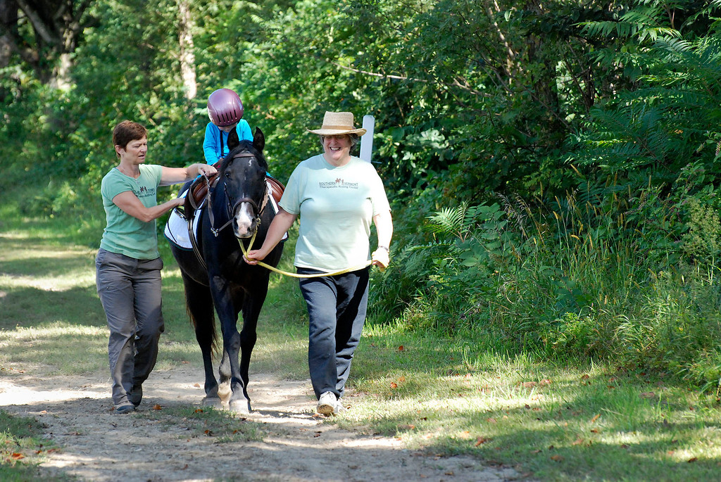 ". Kayla Rice/Reformer                                 Program Director Lorna Young (left) and volunteer Patsy Mehlhop (right) guide the horse ""Spot\"" and rider Lexi Leland, 3, during Lexi\'s weekly horse therapy at Winchester Stables in Newfane."