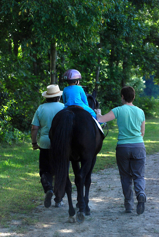 ". Kayla Rice/Reformer                                 Program Director Lorna Young (right) and volunteer Patsy Mehlhop (left) guide the horse ""Spot\"" and rider Lexi Leland, 3, during Lexi\'s weekly horse therapy at Winchester Stables in Newfane."