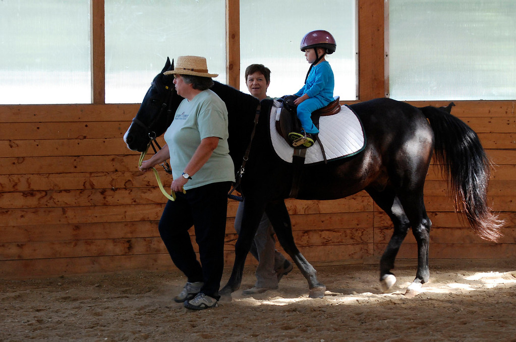 ". Kayla Rice/Reformer                                 Program Director Lorna Young and volunteer Patsy Mehlhop (left) guide the horse ""Spot\"" and rider Lexi Leland, 3, during Lexi\'s weekly horse therapy at Winchester Stables in Newfane."