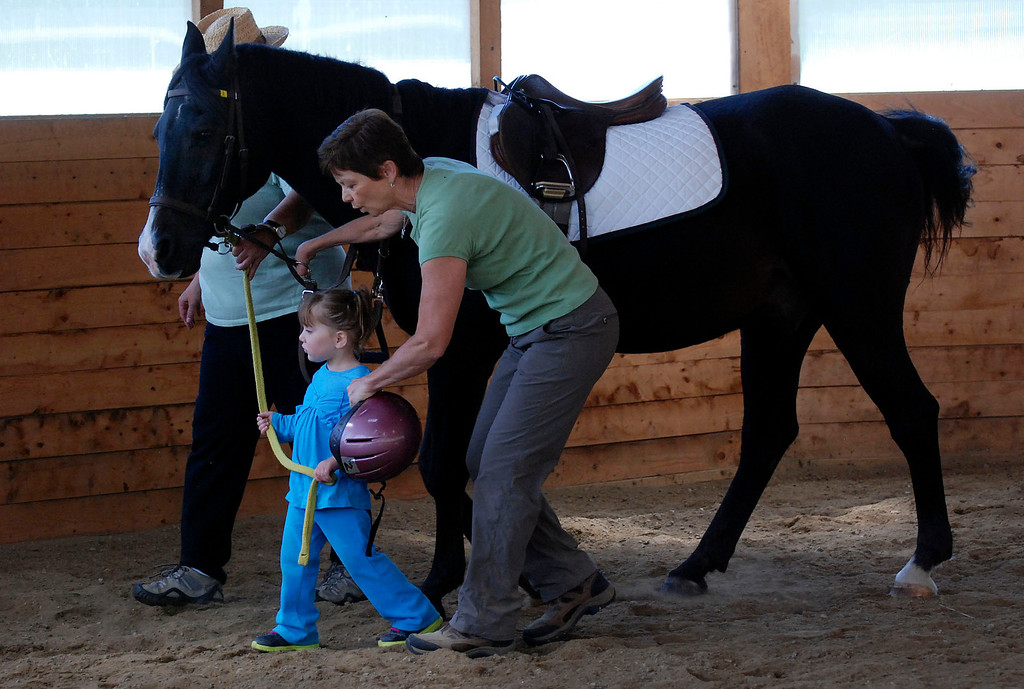 ". Kayla Rice/Reformer                                 Program Director Lorna Young (right) and volunteer Patsy Mehlhop help Lexi Leland, 3, guide therapy horse ""Spot\"" during Lexi\'s weekly horse therapy at Winchester Stables in Newfane."