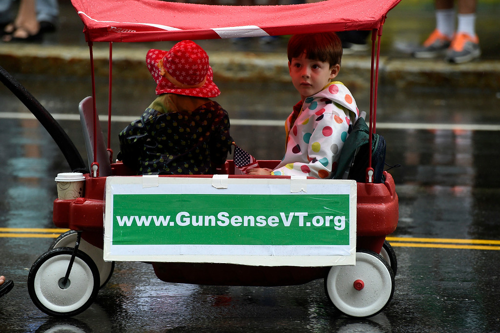 """. Kayla Rice/Reformer Alice and Ethan Braden ride in a wagon with the \""""Gun Sense Vermont\"""" group in the Brattleboro Fourth of July parade on Friday."""