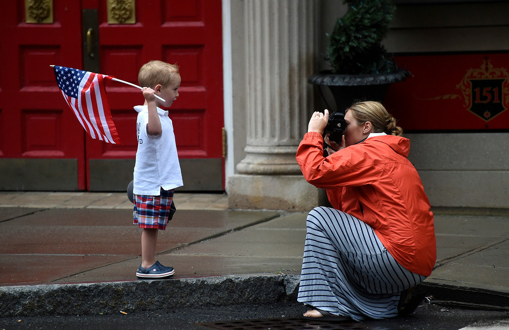 . Kayla Rice/Reformer Lauren Bell of Dummerston takes a photo of her son Colin Bell, 2, while they wait for the Brattleboro Fourth of July parade to begin on Friday.