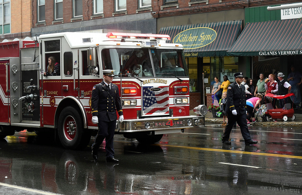 . Kayla Rice/Reformer Members of the Brattleboro Fire Department walk alongside a fire truck in the Fourth of July parade in Brattleboro on Friday.