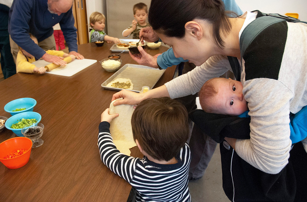 . Kayla Rice/Reformer MJ Iams, 3, of Brattleboro gets some help from his mother, Nara Iams and baby brother Patrick Iams while flattening out his pizza crust during a cooking class held at the Brattleboro Food Co-Op for the Winter Carnival on Friday afternoon.