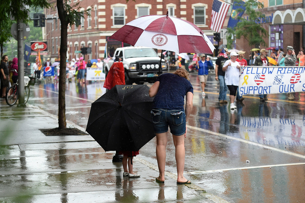 . Kayla Rice/Reformer A young girl holds a large umbrella while she watches the Brattleboro Fourth of July parade with her mother on Friday.