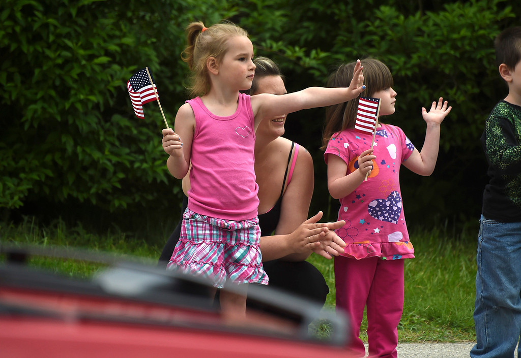 . Kayla Rice/Reformer Cousins Hayla and Maddison Paligo, both 4, stand with Rebecca Paligo and wave at passerby during the Hinsdale Memorial Day parade on Monday morning.