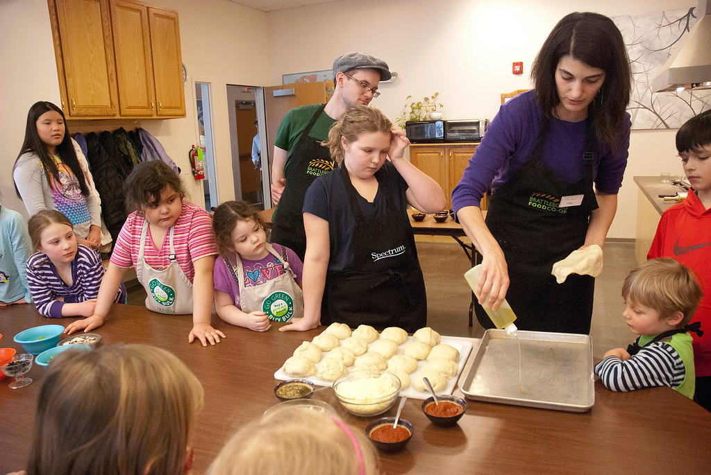 . Kayla Rice/Reformer Brattleboro Food Co-op Education & Outreach Coordinator, Vicky Senni demonstrates how to make a pizza during a Winter Carnival cooking class at the Co-op on Friday afternoon.