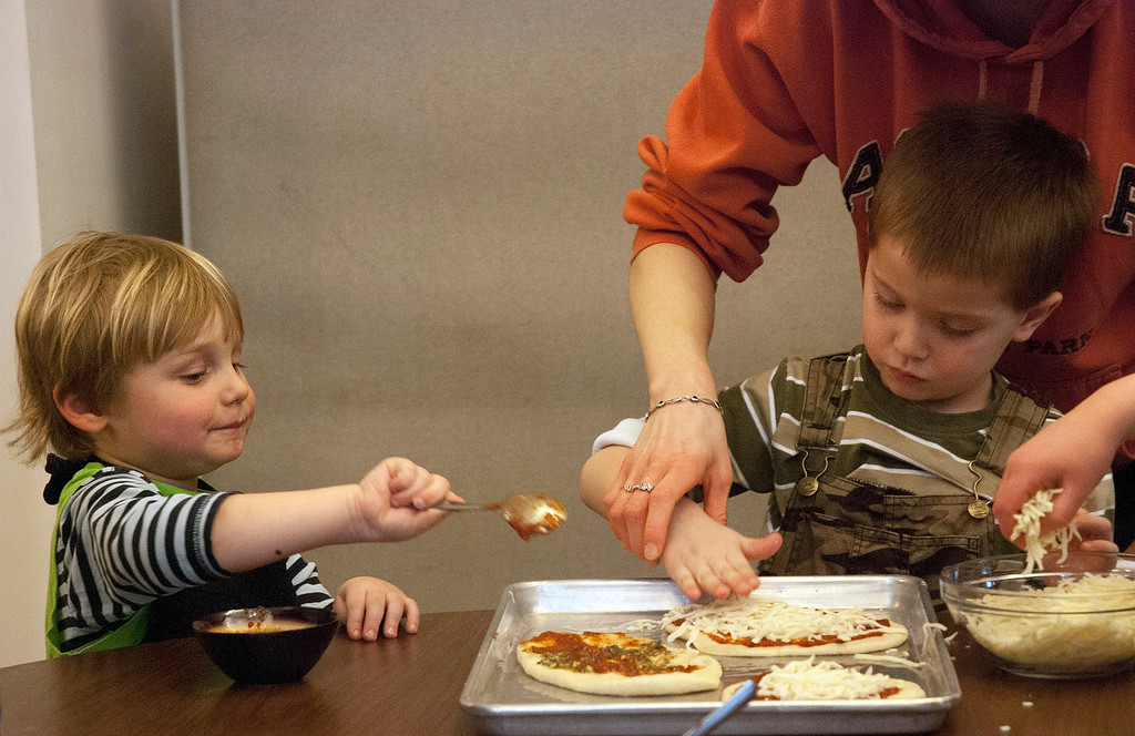 . Kayla Rice/Reformer Rowan Carse, 3, of Brattleboro and Cooper Smith, 5, of Brattleboro decorate their pizza crust with toppings during a cooking class held at the Brattleboro Food Co-Op for the Winter Carnival on Friday afternoon.
