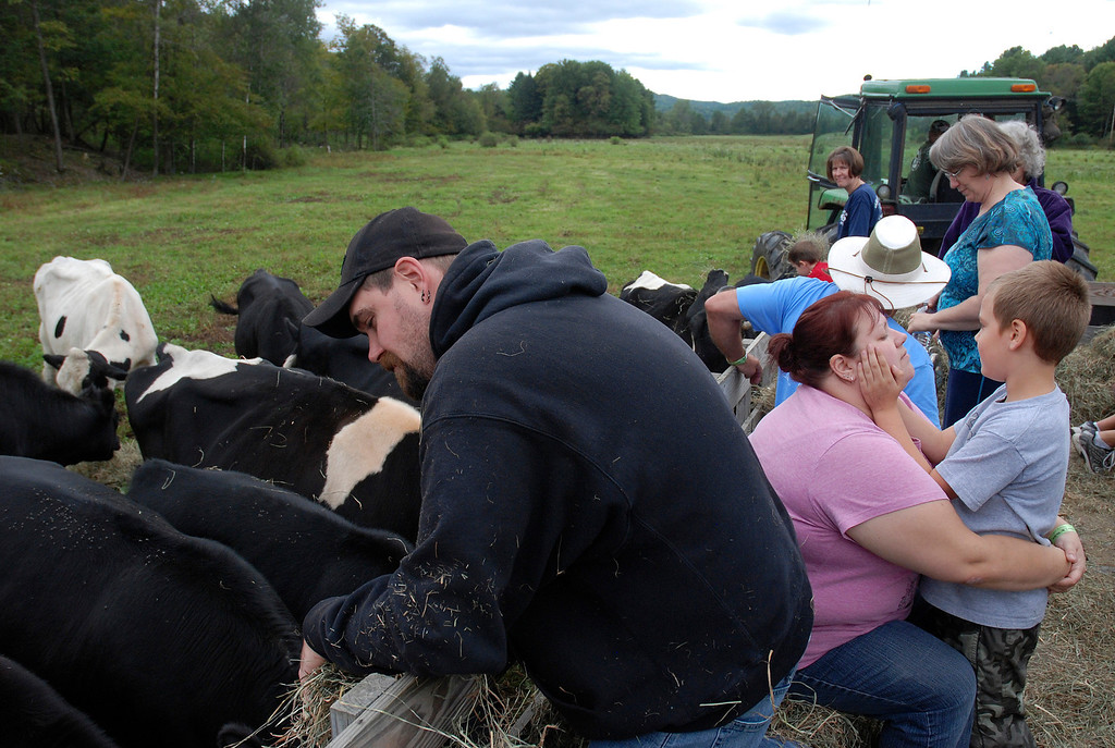 . Kayla Rice/Reformer Chris Tidd feeds cows while on a hayride with his wife Jennifer Tidd and son Jacob Tidd, 6, of Westminster at Gaines Farm in Guilford.