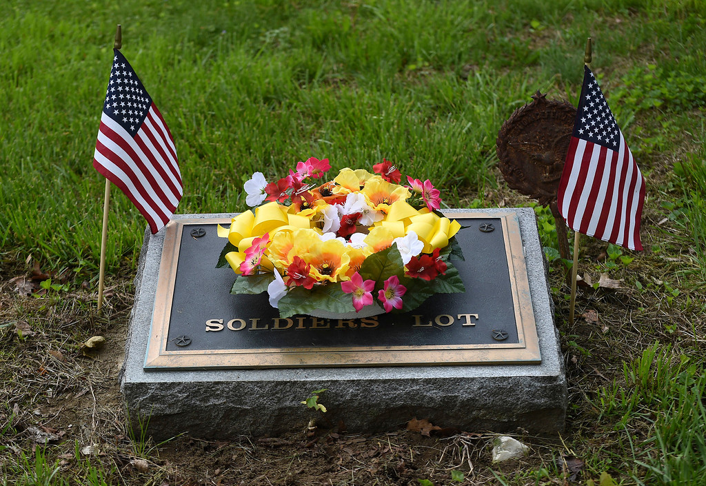. Kayla Rice/Reformer A wreath of flowers is left on the marker for the Soldier\'s Lot at Prospect Hill cemetery in Brattleboro after the Memorial Day service held there on Monday morning.