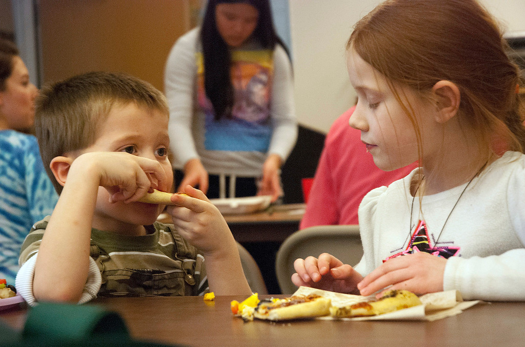 . Kayla Rice/Reformer Cooper Smith, 5, of Brattleboro tries a bite of his sister, Adelaide Smith, 7,\'s pizza during a cooking class held at the Brattleboro Food Co-Op for the Winter Carnival on Friday afternoon.
