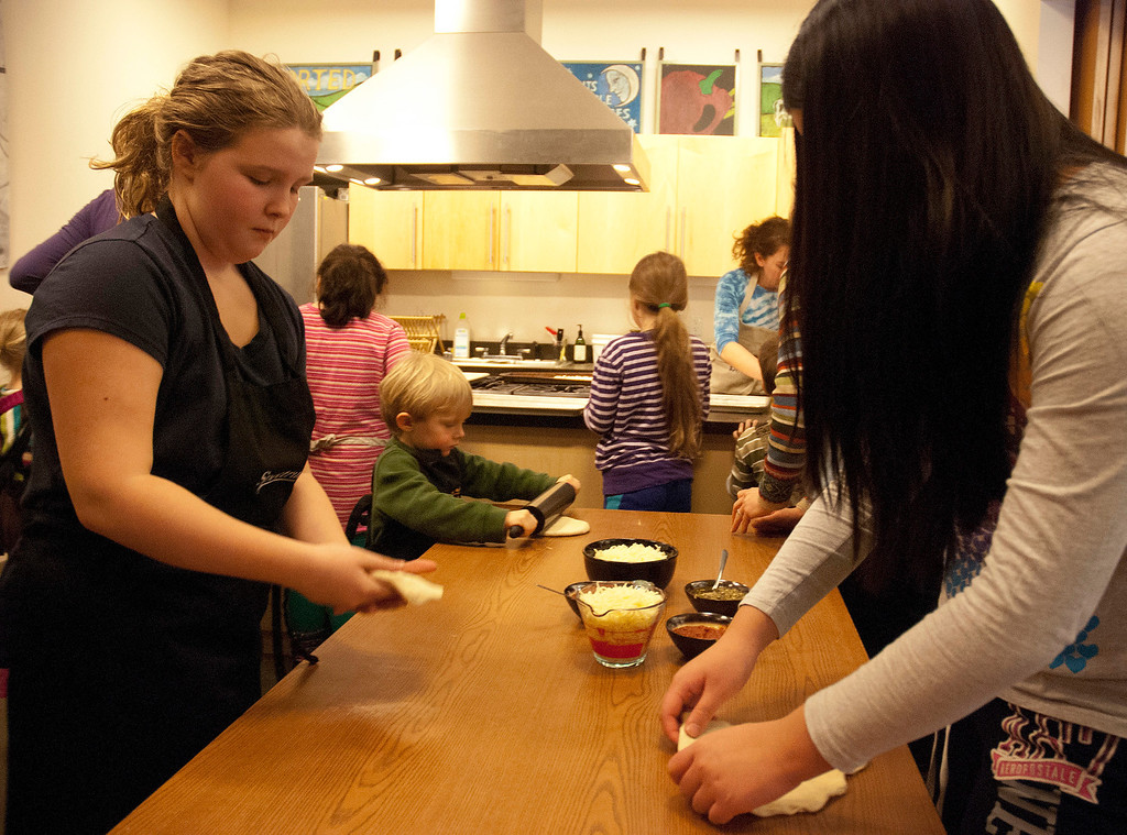 . Kayla Rice/Reformer (L-R) Hannah Lane, 10, of Brattleboro and Katrina Tao, 11, of Brattleboro flatten out their pizza dough during a cooking class held at the Brattleboro Food Co-Op for the Winter Carnival on Friday afternoon.