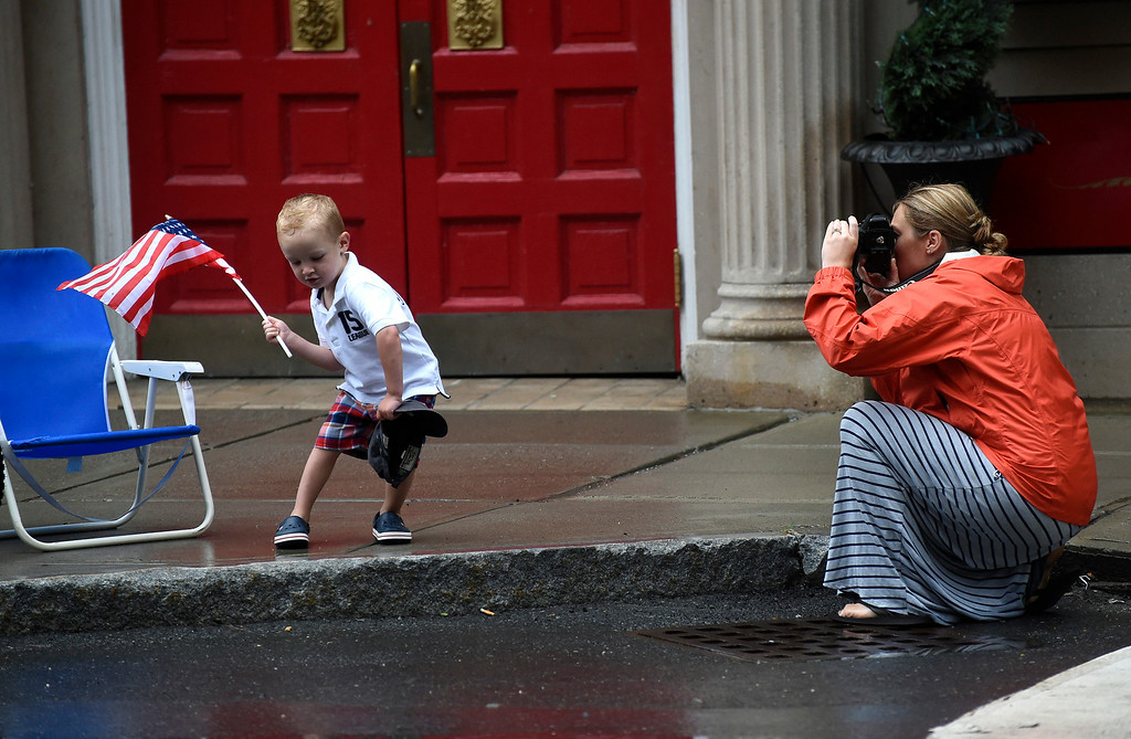 . Kayla Rice/Reformer Lauren Bell of Dummerston takes a photo of her son Colin Bell, 2, as he energetically waves an American flag while they wait for the Brattleboro Fourth of July parade to begin on Friday.